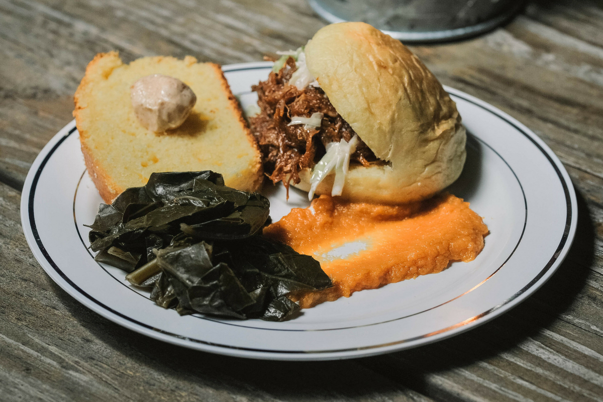 catered meal with pulled pork sandwich, puree, collared greens and bread